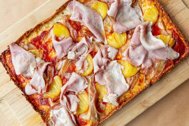 Detroit-style pizza topped with pineapple and ham