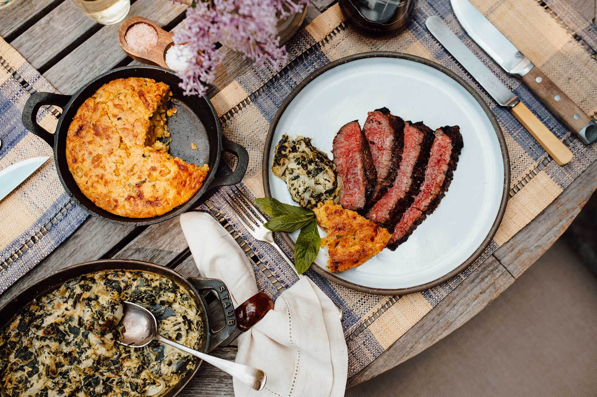 Cleaver Meat Co. flank steak and cornbread on a table set with flowers and a placemat
