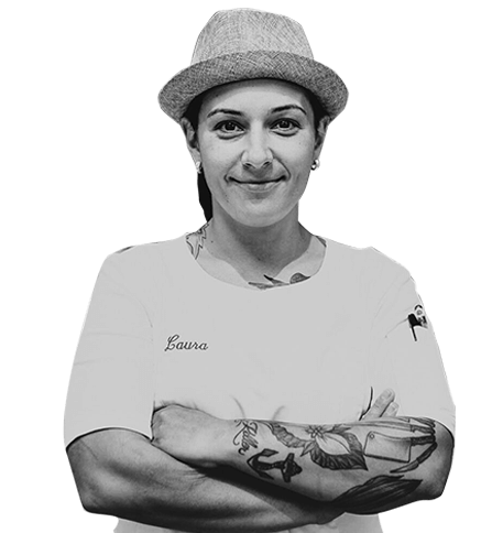 Chef Laura Petracca with her arms crossed leaning against a bar