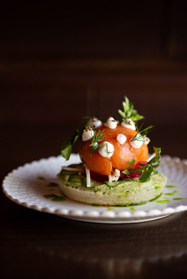 Smoked Salmon served on a crumpet with cucumber, fresh herbed quark, on a decorative white plate