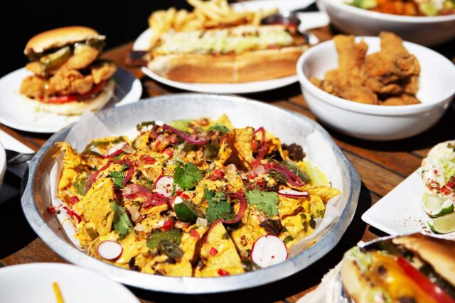 platter of nachos on wooden table among other dinner dishes