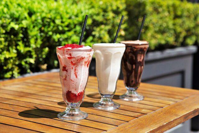 strawberry milkshake, vanilla milkshake and chocolate milkshake in a row on outdoor wooden table with long paper straws