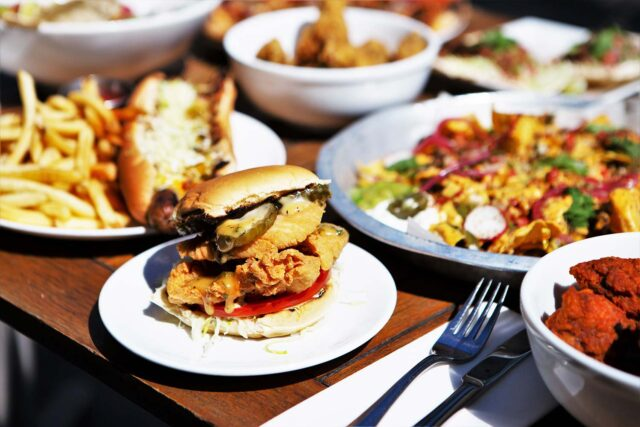 fried chicken sandwich on single white plate and bowl of crispy fries farther on wooden table