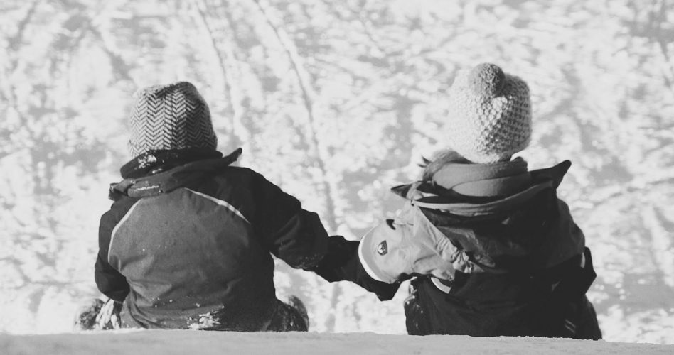 Black and white image of two kids playing in the snow