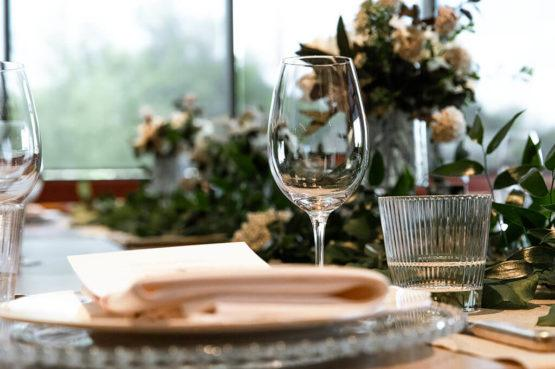 A close up of the table setting in Buffo's private dining room with a beautiful dish and wine glass in the foreground, and foliage and flowers in the background.