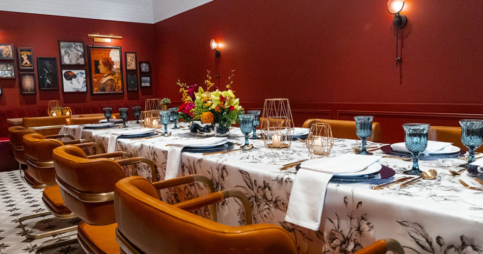 Buffo's Private Dining Room set up with an embellished tablecloth, blue glassware, bright florals and candles.