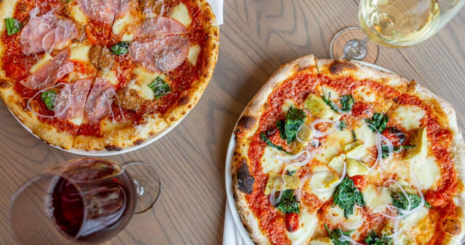 Two glasses of wine and two pizza features from YYC Food & Drink Experience