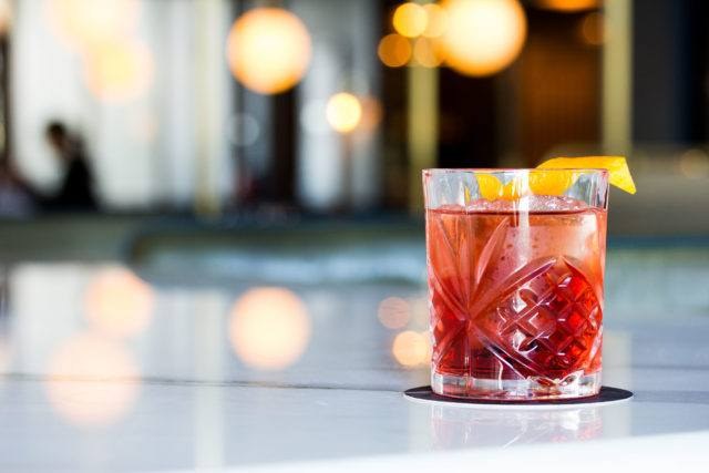 Classic negroni cocktail sitting on the white marble bar at Parcheggio.