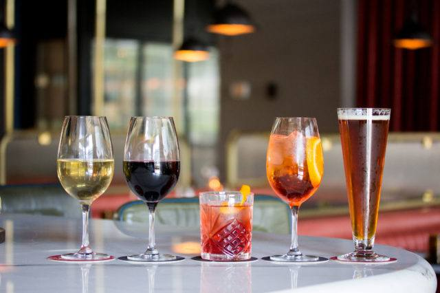 A glass of white wine, red wine, a Negroni, an Aperol spritz and a glass of beer on the Parcheggio bar.