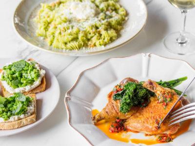 Brick-pressed cornish hen, housemade fussili and summer pea bruschetta on a table at Parcheggio.