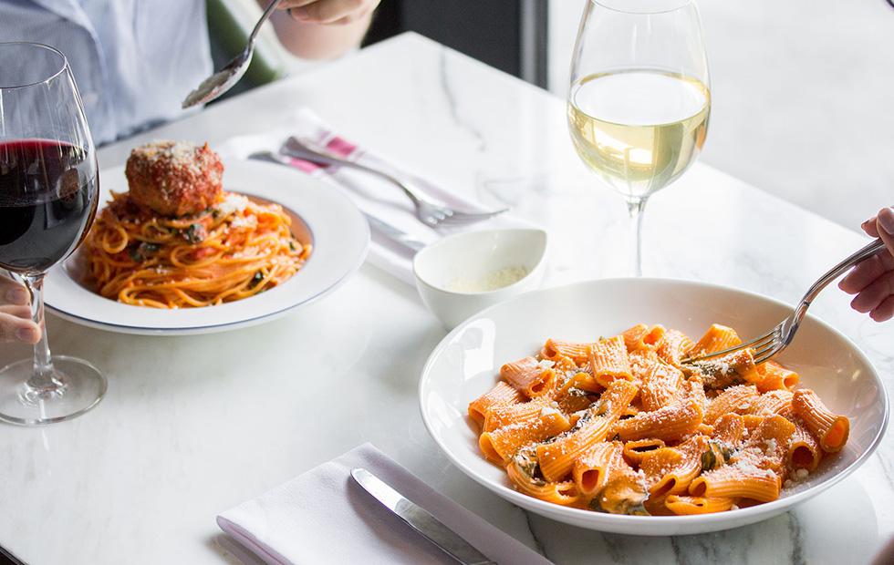 Parcheggio pasta dishes - one rigatoni and one spaghetti and meatball dish on a marble table with two guests dining. A wine glass sits in front of each guest.