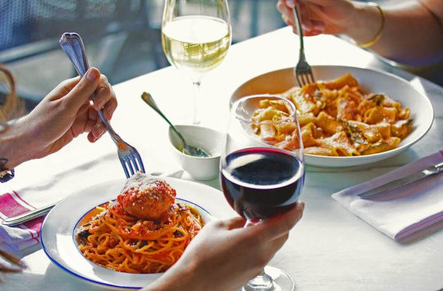 Two people sharing a meal. View is of the two pasta dishes and a glass of red wine with a hand on it.
