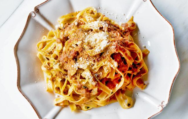 Top view of tagliatelle pasta with sauce and parmigiano cheese on top.