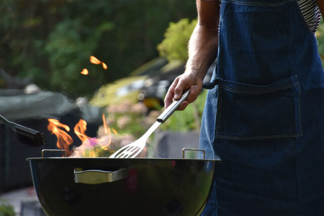 Man cooking at a grill wearing a navy blue apron