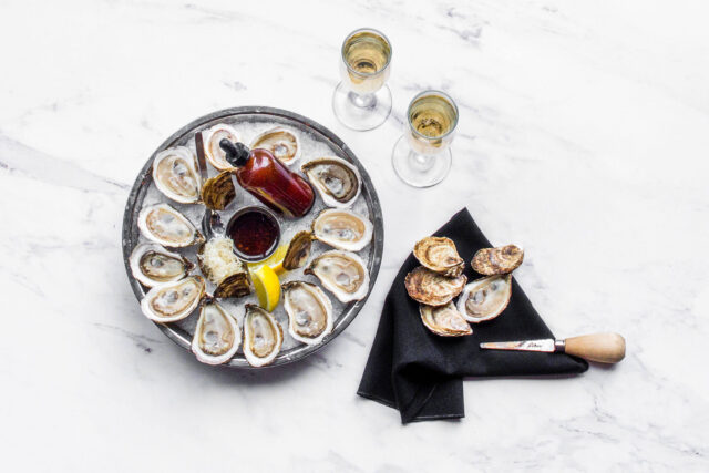 Buck-a-shuck oysters on a white marble table from Parcheggio in Toronto