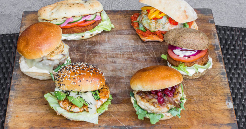 Six burgers in a circle on a wooden cutting board for Burgerfest 2019 at Beaumont Kitchen