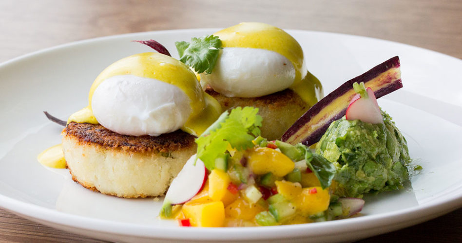 Eggs Benny on a plate with sides