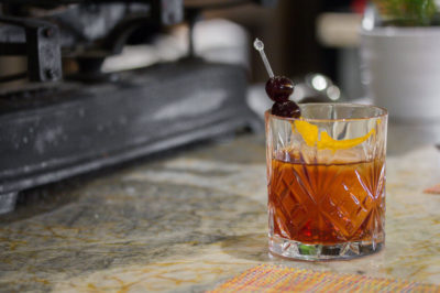 Old Fashioned cocktail in a rocks glass garnished with cherries and an orange twists