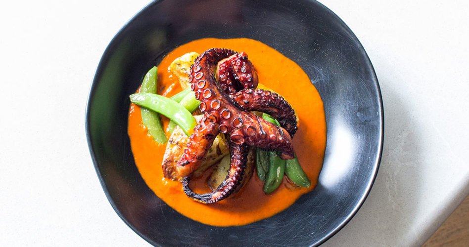 Braised Octopus Gallego with roasted patatas. snap peas and Spanish Paprika sauce. In a black bowl on a white tabletop.