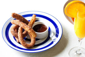 Barcelomont menu item - churros served on a blue and white plate with spiced chocolate dipping sauce, next to a mimosa