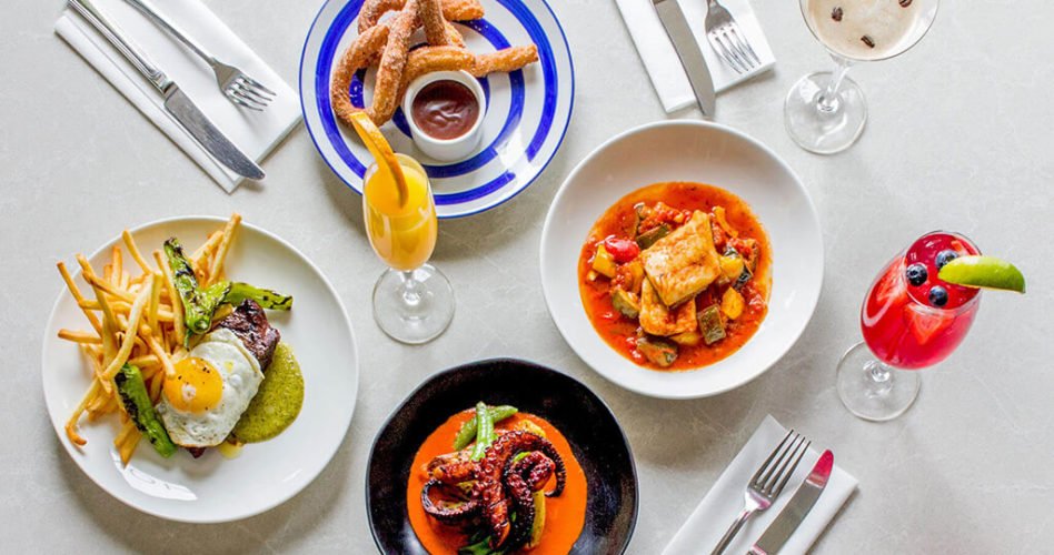 A top view of four dishes that are part of the Barcelomont menu. Churros, steak, octopus and salt cod.
