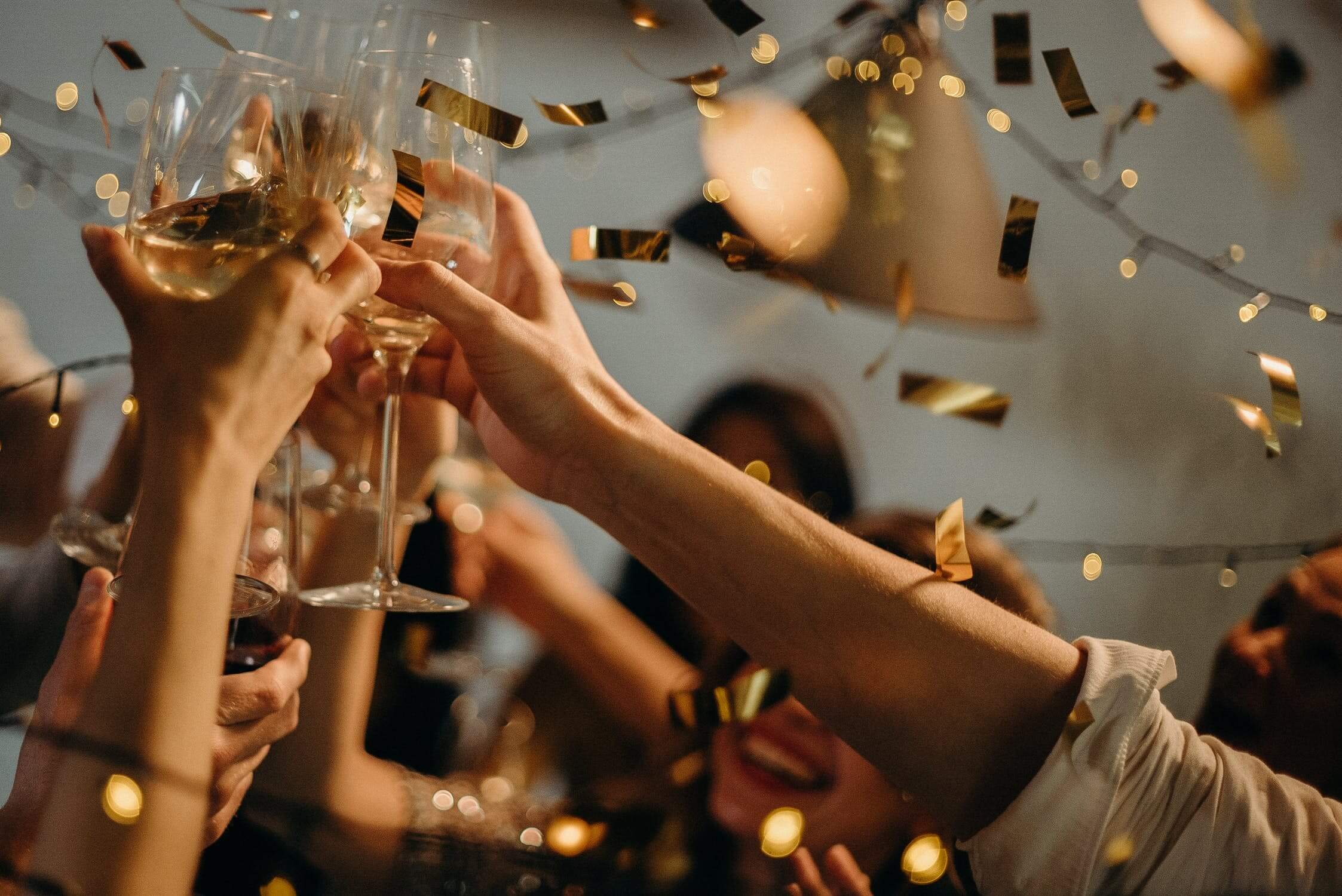 Hands clinking together champagne glasses with gold confetti falling