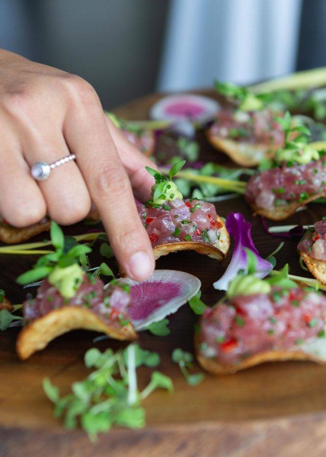 hand picking up canape off wooden tray at arcadian event venue