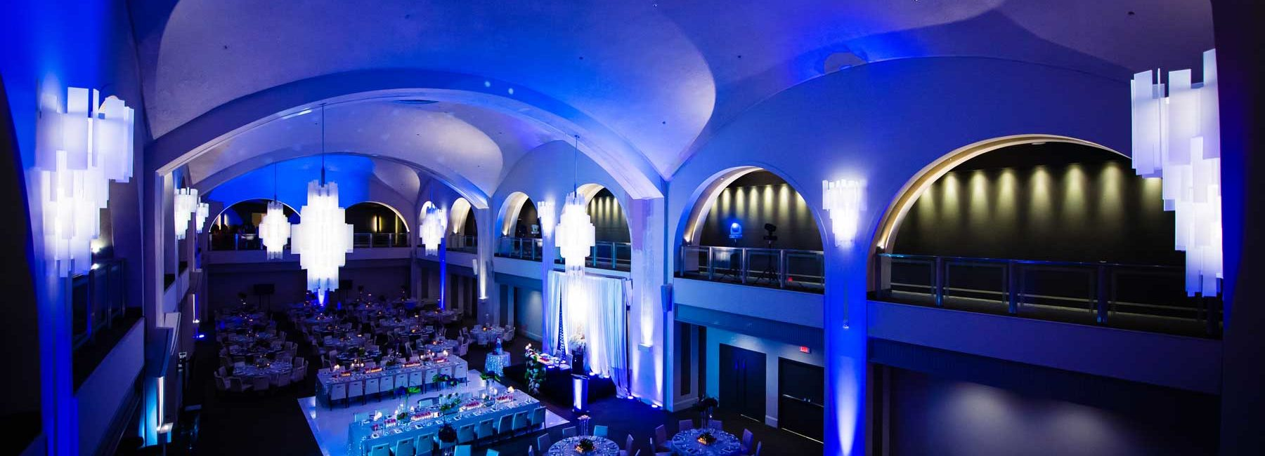 a dark blue lit event space with glamorous chandeliers and dining tables