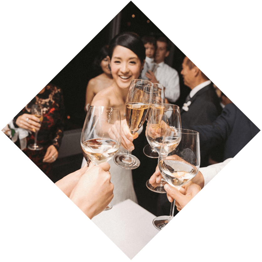 a bride toasting a champagne glass with 4 other champagne glasses while guests watch in the background