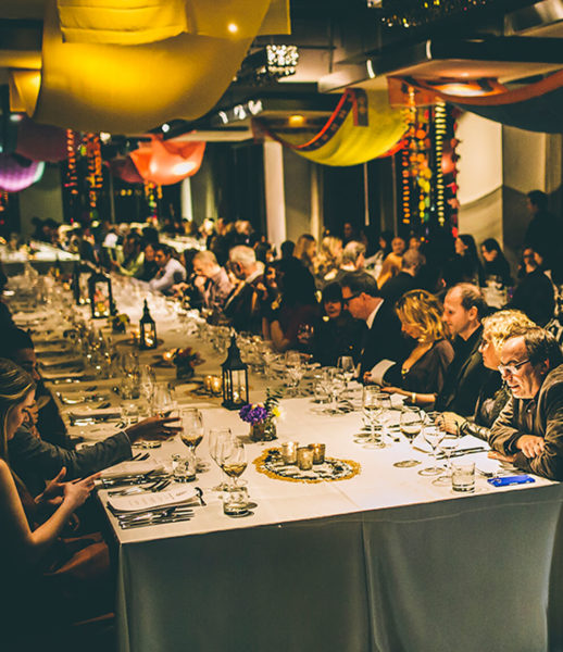 harvest tables with people at arcadian loft with colourful banner hung on the ceiling