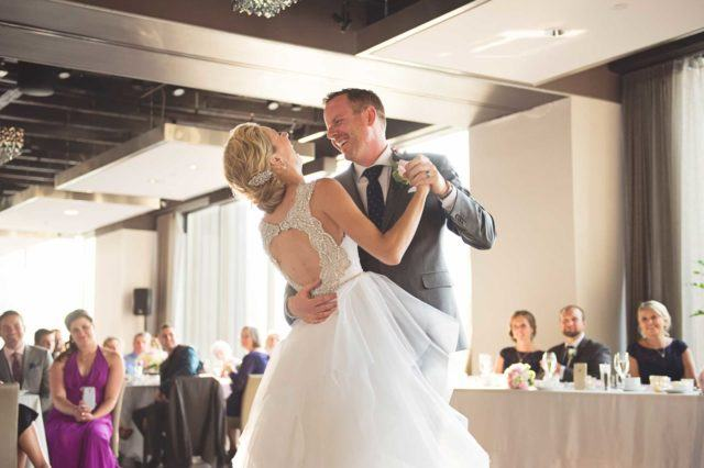 A bride and groom sharing a first dance and smiling at one another at Arcadian Loft