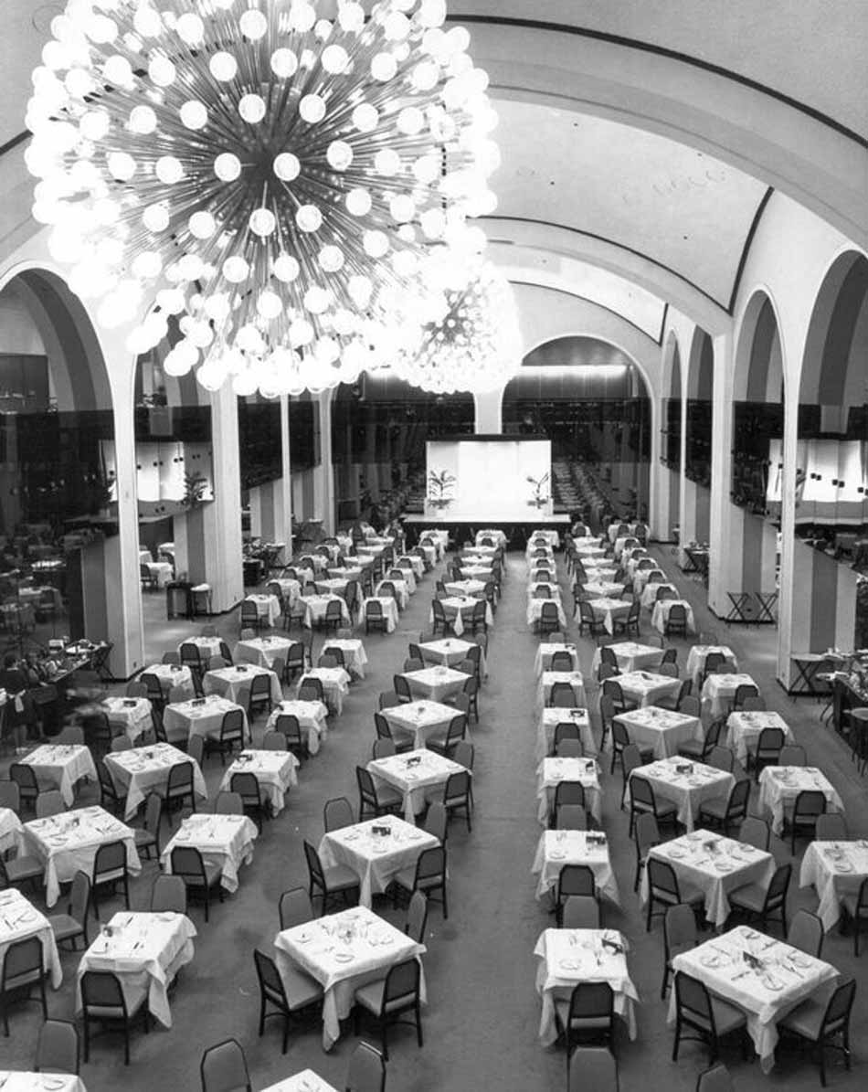 vintage 1962 photograph of arcadian's large event venue holding many dining tables under circular chandeliers