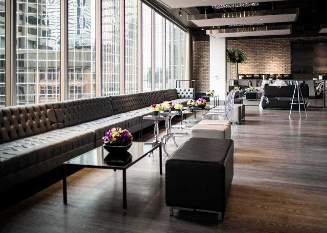 large event space with floor to ceiling windows, brick walls, tables and chairs, and a wall-length leather couch