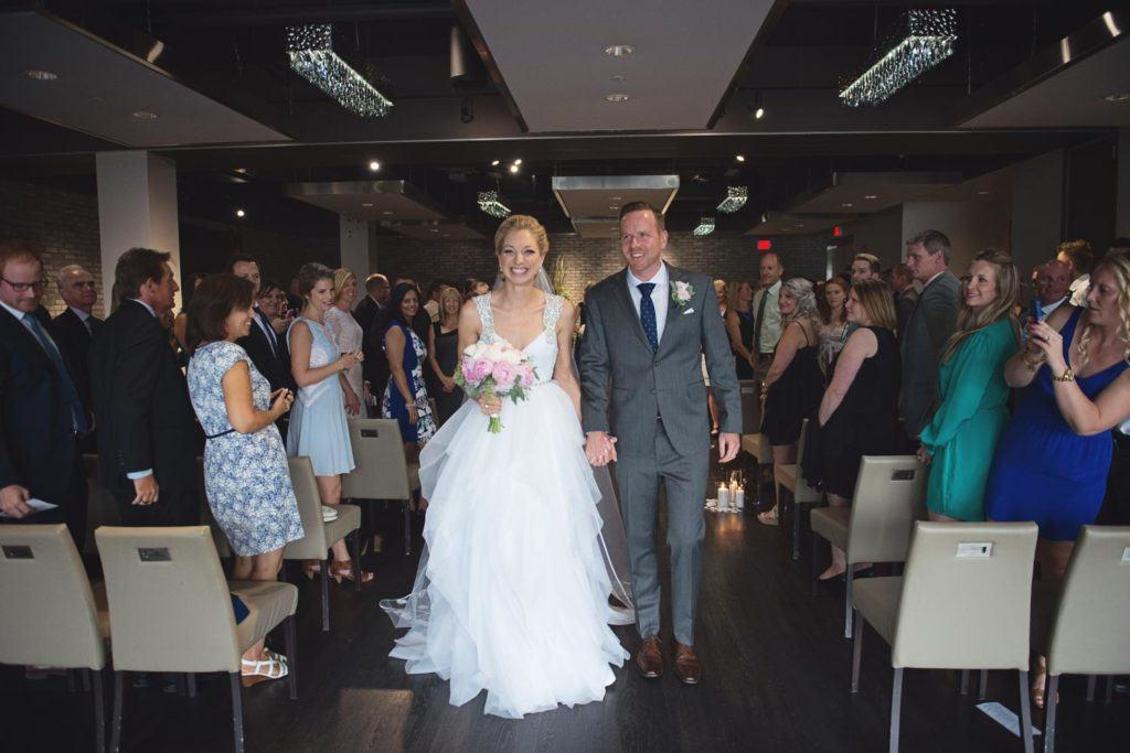 a bride and groom walking down the aisle at Arcadian Loft, smiling while their guests cheer