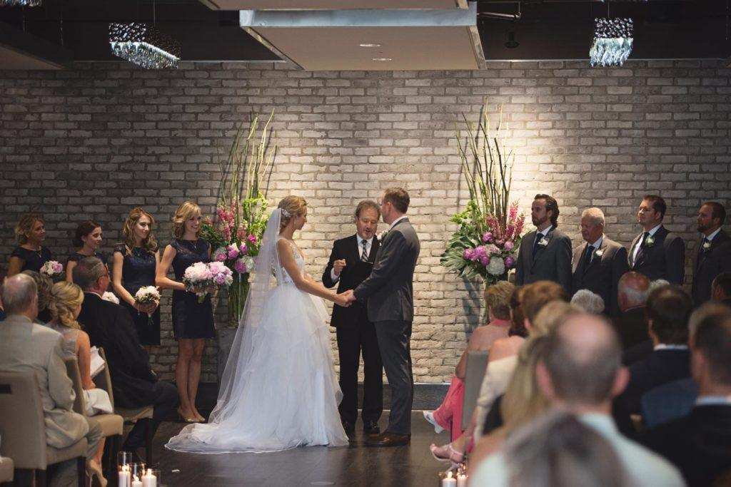 Bride and groom holding hands during ceremony at Arcadian Loft