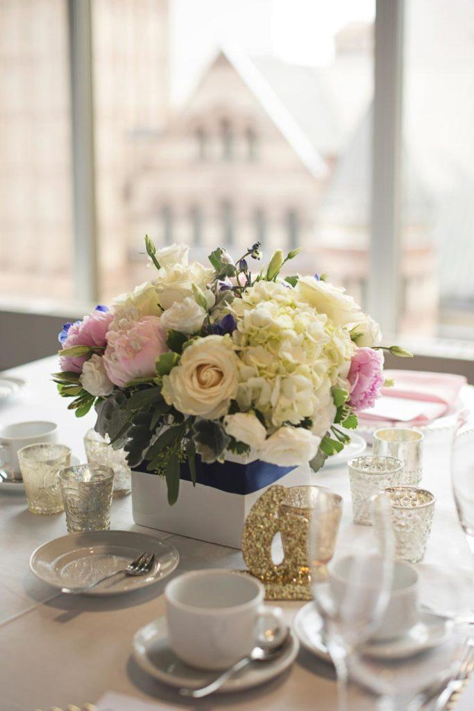a close up shot of a wedding flower arrangement near a window opening to the historic street