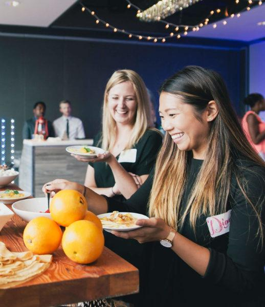 two women grabbing food from food station at arcadian loft