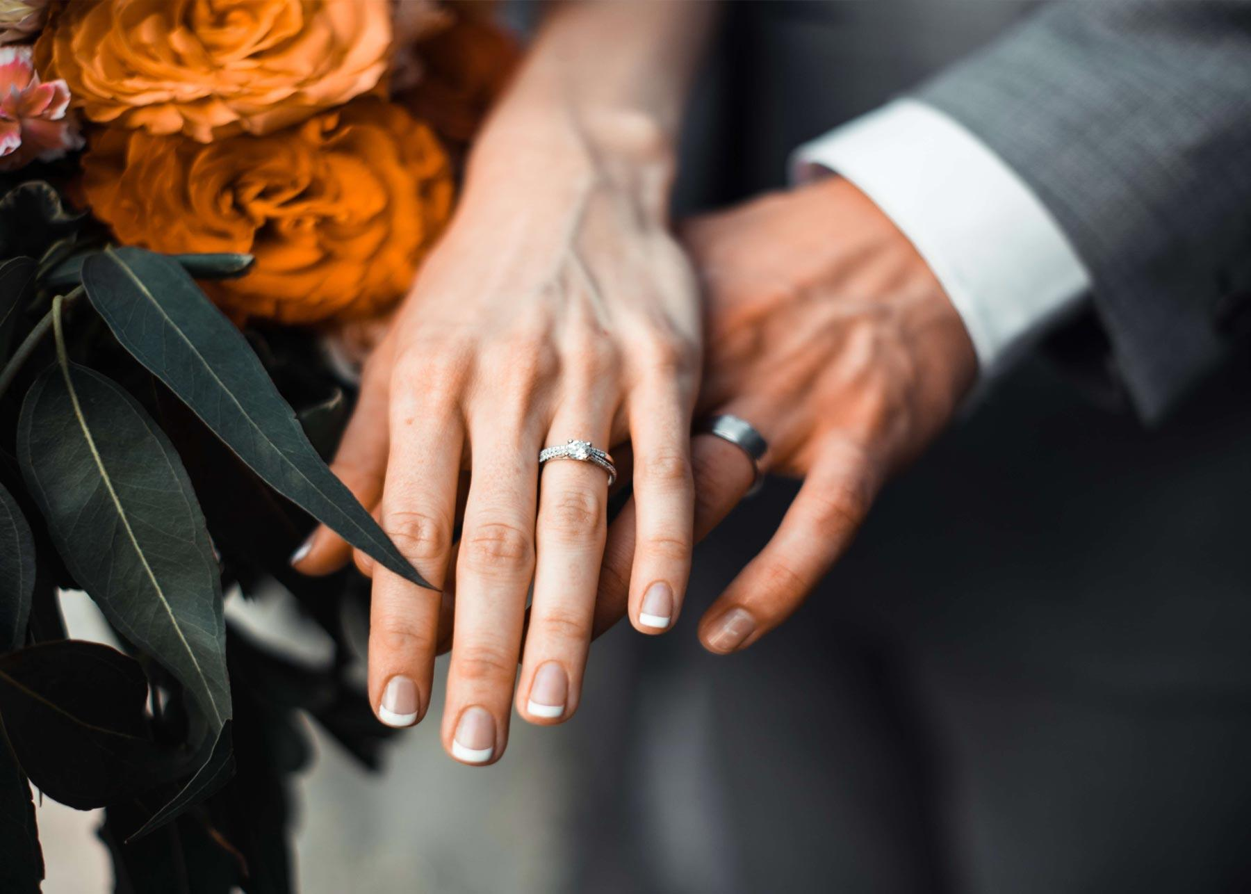 closeup of hands with silver wedding rings and flower bouquet