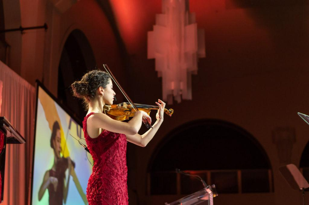 Close-up shot of violinist performing on stage in Arcadian Court in Toronto