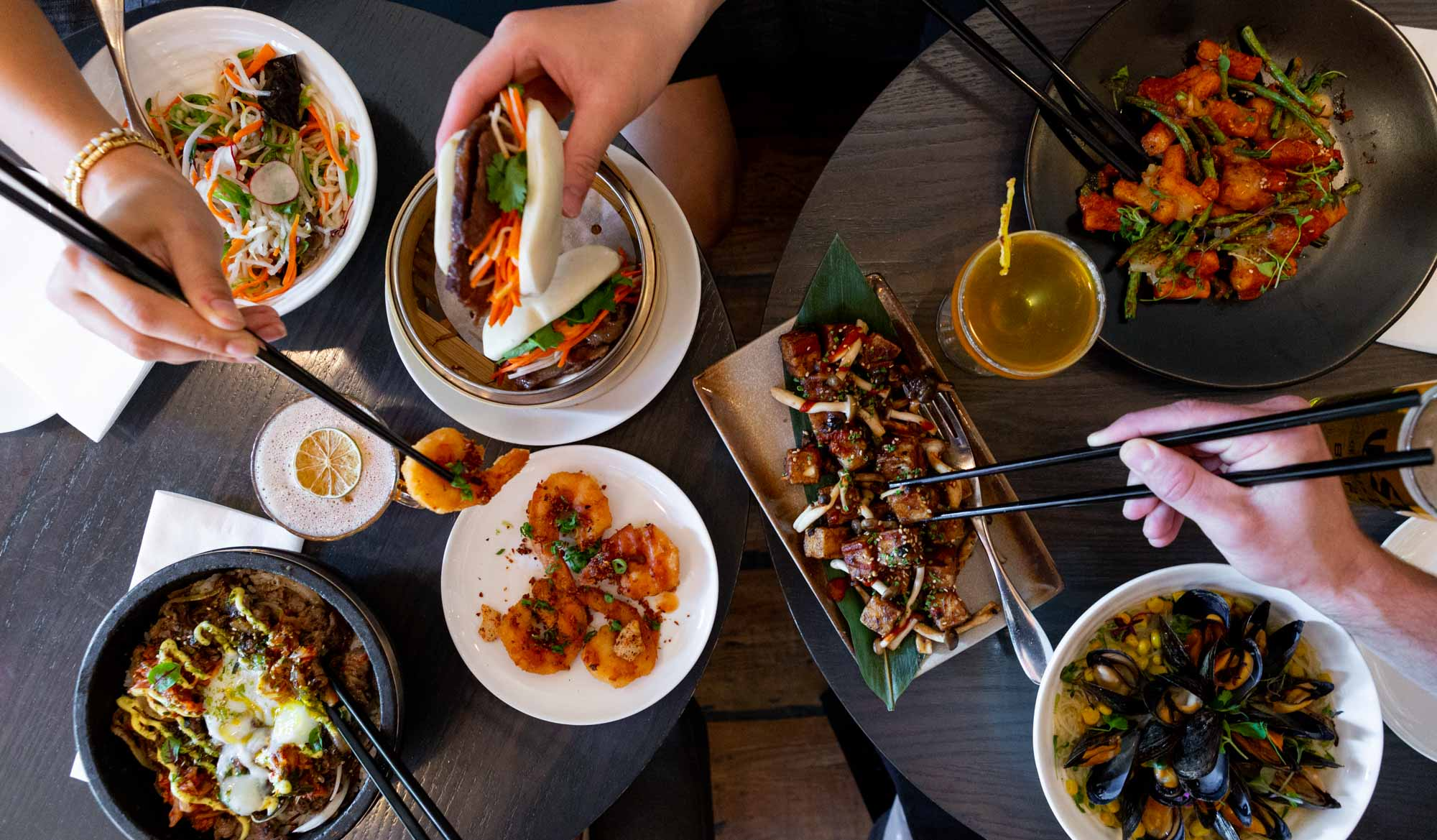 Summerlicious R&D two tables filled with Asian Canadian dishes with multiple diners and chopsticks