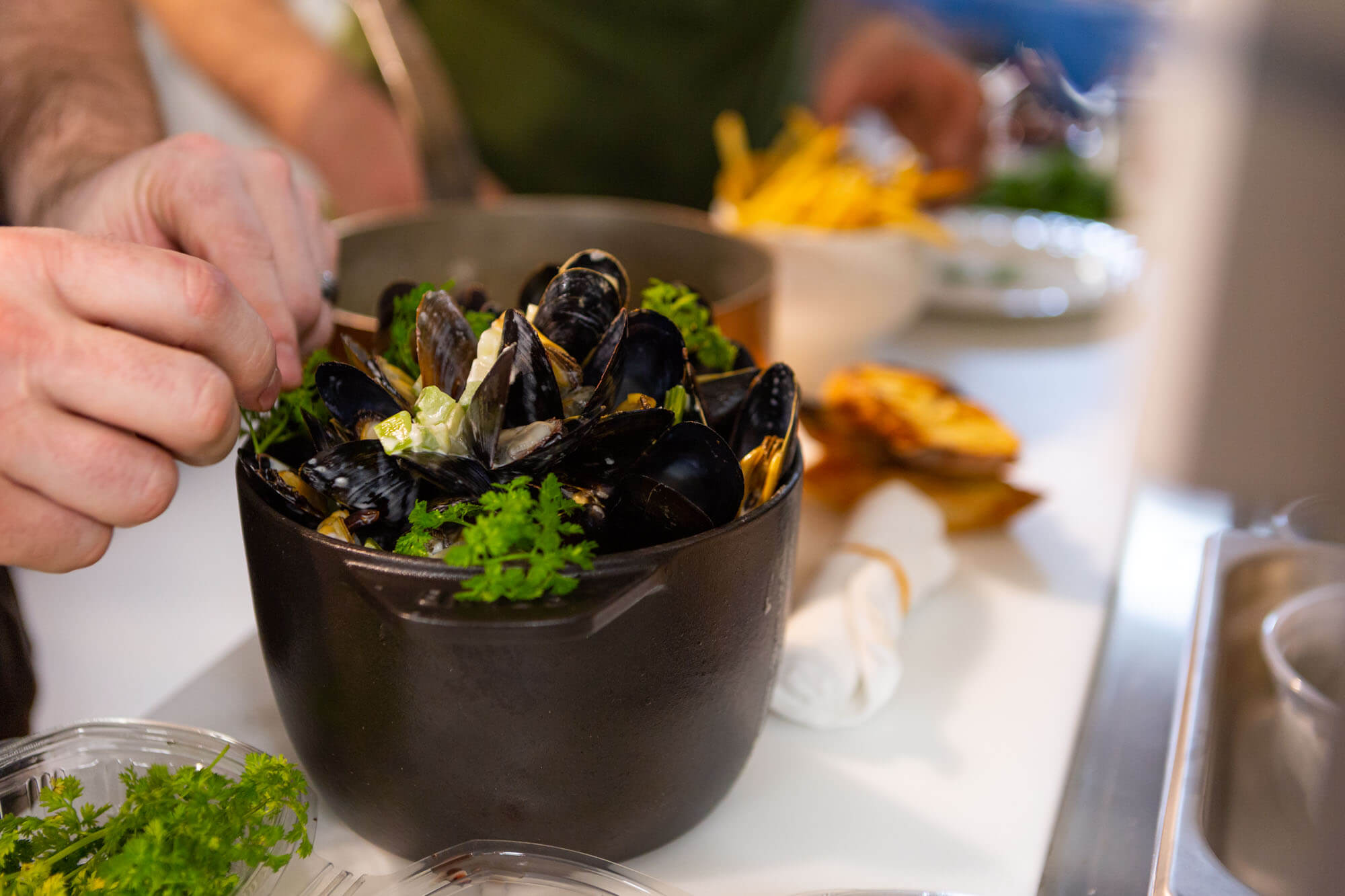 Chef placing garnishes on moules frite in the Maison Selby kitchen