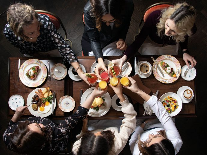 An overhead shot of six friends cheersing mimosas and Caesars over a table of brunch food at Maison Selby
