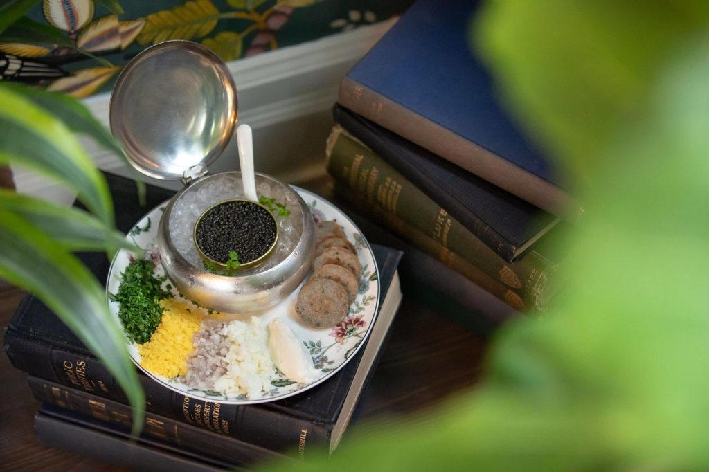 Serving dish with caviar and garnishes sitting on a stack of books at Maison Selby