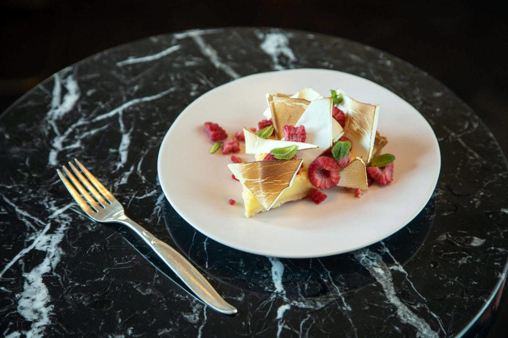 Lemon tart garnished with raspberries on a white plate at Maison Selby