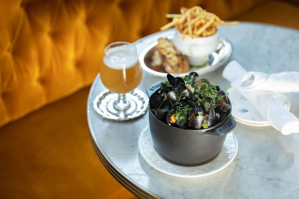 Moules Frites and a glass of beer on a table at Maison Selby