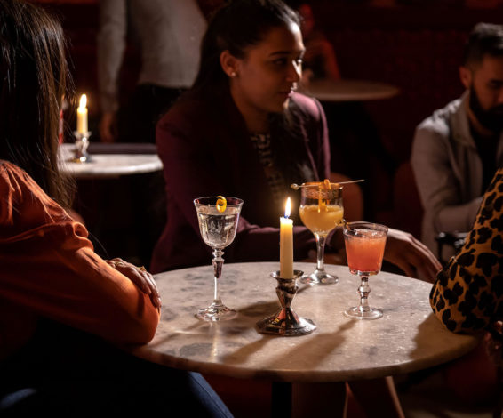 Guests drinking cocktails at a candlelit table at Sous Sol, Maison Selby's speakeasy cocktail bar