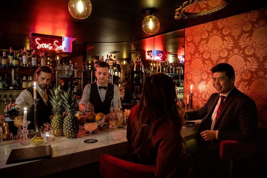 Guests drinking and bartenders working a Sous Sol, Maison Selby's speakeasy cocktail bar