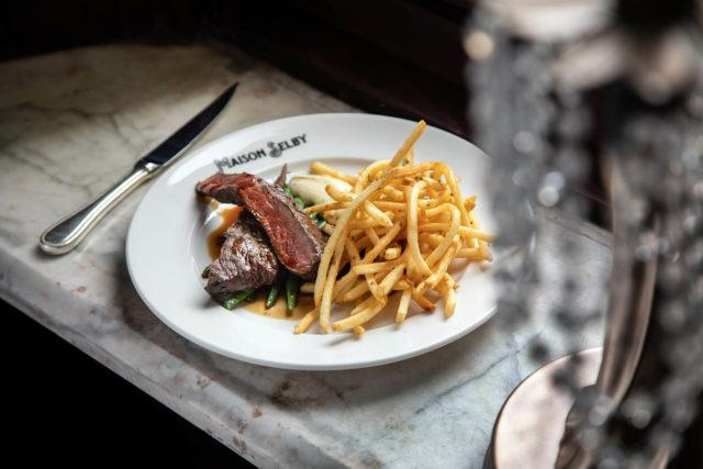 A plate of Steak Frites and flatware at Maison Selby in Toronto