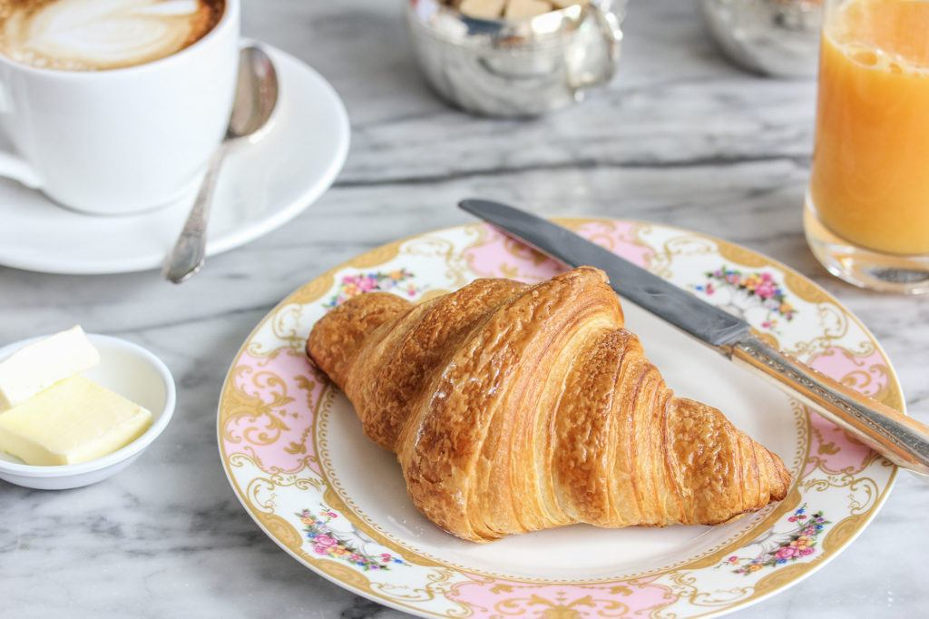Croissant, coffee and juice sitting on the bar at Maison Selby