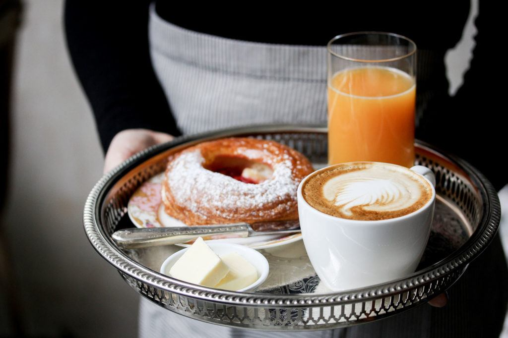 a waitress serving a cappuccino, juice and baked treat on an antique silver tray